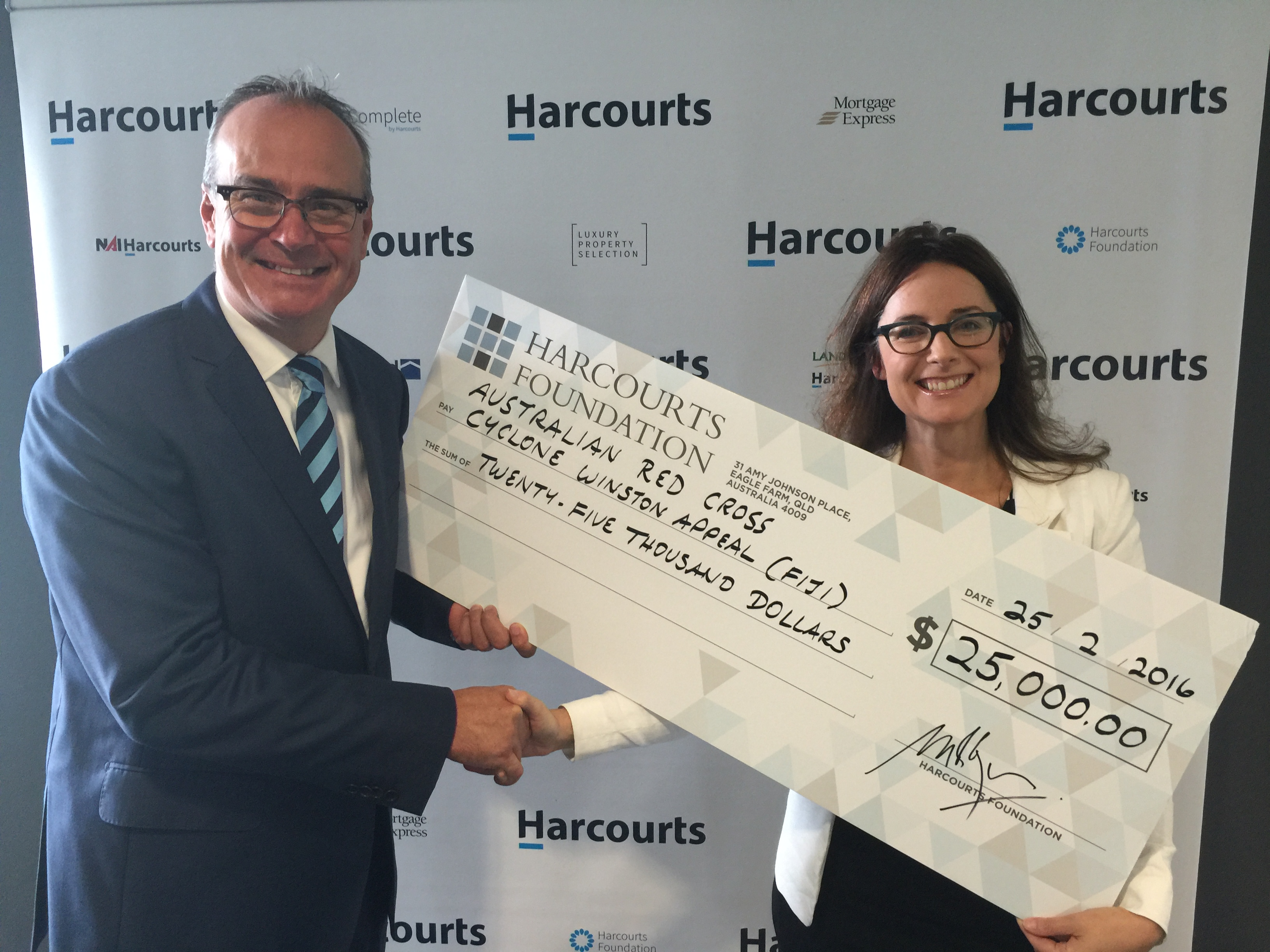 Harcourts Australian Operations Manager, Marcus Williams, presents the donation for Fiji recovery efforts to Red Cross Australia's Trusts and Foundation Manager, Belinda Collins.